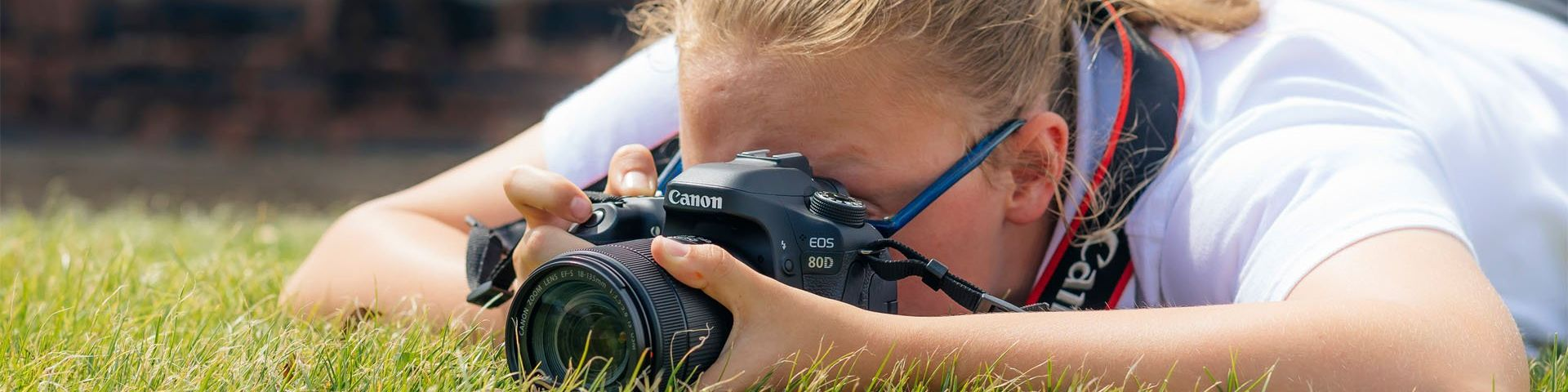 A girl lies on the grass, her face obscured by a Canon EOS 80D, as she takes a shot